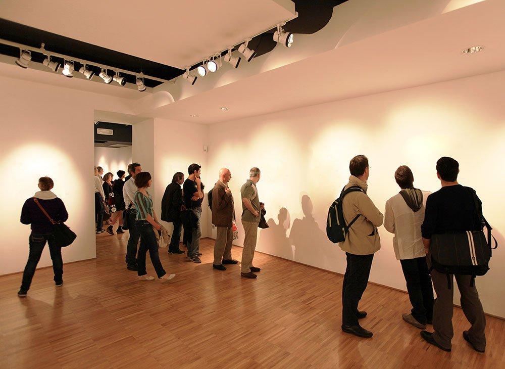 Persone davanti alle opere di Lana Newstrom nella sua esibizione arte invisibile