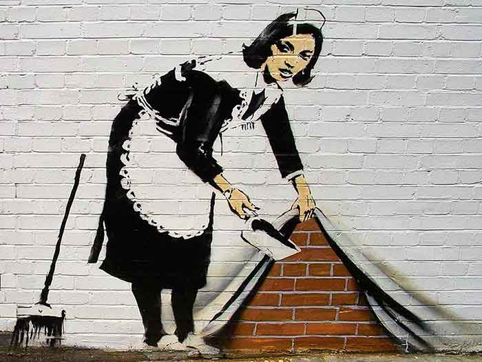 Graffito di Banksy: domestica che nasconde la polvere sotto il tappeto