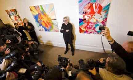 Damien Hirst in posa davanti ai fotografi in mezzo a due sue opere da Sothebys